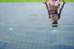 Reflection young woman enjoying a swimming pool Royalty Free Stock Image