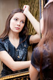 Reflection of young woman in a mirror Royalty Free Stock Photography