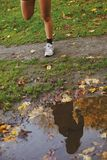 Reflection of young woman in a puddle of water in park Stock Image