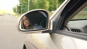 Reflection of a young woman in a side mirror of a car, she straightens her hair. Beautiful woman looking in car back rear-view mirror sitting in vehicle. Slow stock video