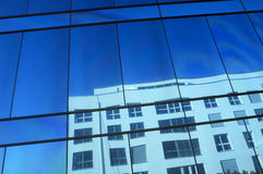 Reflections. The reflection of a white building in the blue glass frontage of another building. Nyon, Switzerland Stock Photos