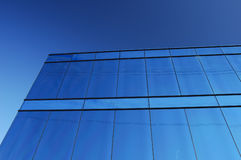 Reflections. A modern office block with a glass facade reflects the clear blue of a cloudless sky, with some power lines Stock Photo