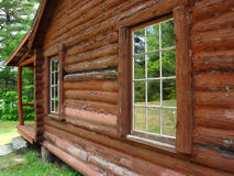 Reflections. The windows of a log cabin reflecting the scenery stock photography