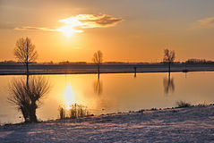 Reflections in the afternoon sun. A glance across the river at the end of the afternoon at sunset. Due to the orange colored light the snow color is abnormal. On Royalty Free Stock Image