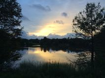 Reflections as the sun sets. Sunset shot near a pond Royalty Free Stock Photo
