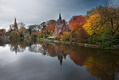 Reflections of Autumn. The colors of autumn reflected in the water in a park in Bruges Stock Photography