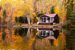Reflections of a autumn forest and a house in a lake Royalty Free Stock Photo