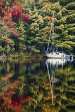 Reflections of Autumn. A single sailboat with reflection docked on Mary Lake in autumn Royalty Free Stock Image