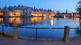 Reflections of the Binnenhof 13 century gothic castle on the Hofvijver lake at dusk during the blue hour. With the clock tower of Grote of Sint Jacobskerk on royalty free stock photos