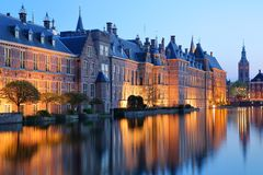 Reflections of the Binnenhof 13 century gothic castle on the Hofvijver lake at dusk during the blue hour. With the clock tower of Grote of Sint Jacobskerk on royalty free stock photography