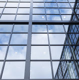 Reflections of blue sky and clouds in glass facade of modern off Royalty Free Stock Photo