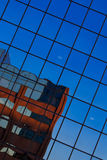 Reflections. Blue sky and partial building reflected on windows of a modern glass building creating abstract shapes and pattern Stock Photos