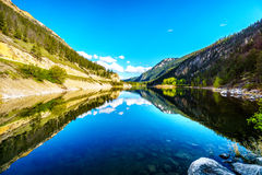 Reflections of blue sky, trees and mountains in the smooth surface on the crystal clear water of Crown Lake Stock Image