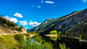 Reflections of blue sky, trees and mountains in the smooth surface on the crystal clear water of Crown Lake Stock Images