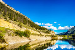 Reflections of blue sky, trees and mountains in the smooth surface on the crystal clear water of Crown Lake Stock Photo
