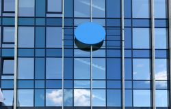 Reflections of the blue sky in the windows of a standard office. Building. Sunny day royalty free stock photo