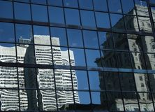 Reflections of buildings. Skyscraper glass panels reflecting other modern building royalty free stock image