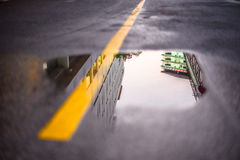 Reflections of buildings in puddles on the road. Stock Photo