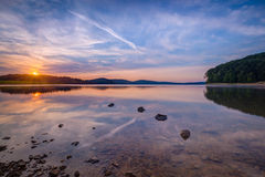 Reflections in a calm lake at sunrise Stock Photos