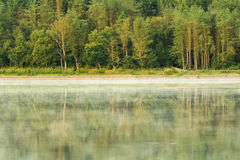Reflections In Calm Misty Water At Lake. Stock Photo