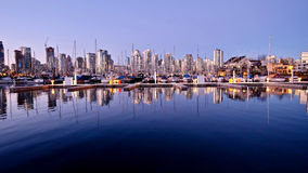 Reflections of city lights and boats in calm water. Royalty Free Stock Image