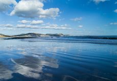 Reflections of clouds on beach at Lyme Regis, Dorset. Reflections of clouds on beach at Lyme Regis in Dorset  with Jurassic Coast cliffs in background Stock Image