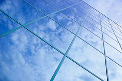 Reflections of clouds and blue sky in facade Stock Photo