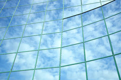 Reflections of clouds and blue sky in facade Stock Image