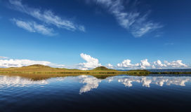 Reflections of clouds and land on a lake Royalty Free Stock Photo