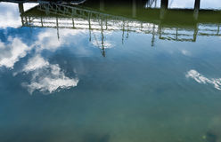 Reflections of clouds and sky plus pier Stock Photo