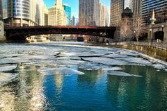 Reflections of colorful Chicago cityscape on a frozen chicago river with ice chunks floating under a bridge Royalty Free Stock Photography
