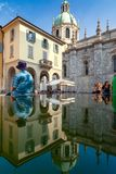 Reflections of Como Cathedral. The Cathedral of Como reflected together with people sitting over a plain fountain, Lombardy, Italy stock images