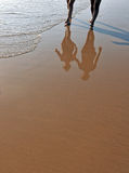 Reflections of a couple walking on the beach Costa Ballena, Rota, Cadiz province,Spain Royalty Free Stock Photography