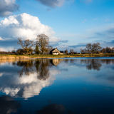 Reflections of coutry house in the lake water. Reflections of coutry farm house and clouds in the lake water Stock Photo