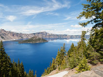 Reflections in Crater Lake. Sky, clouds and mountains reflected in the still water of Crater Lake, Oregon with Wizard Island in the center Stock Image