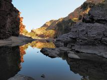 Reflections in the dark waters of Ormiston Gorge with red glowing cliffs Royalty Free Stock Image