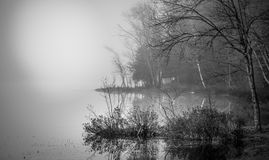 Reflections in early morning fog on a lake near Ottawa, Ontario. Stock Photos