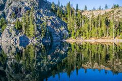 Reflections 2. An early morning photograph of Kangaroo Lake in Northern California.   The Glassy water creates a mirror image of the trees and mountains in the Royalty Free Stock Images