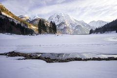 Frozen lake covered in snow with snowy mountain in the back stock photography