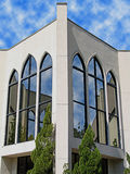 Reflections In Glass. The front of a church in Valdosta GA, USA. The reflections that you see in the windows is the other parts of the church. Clouds were added stock photography