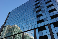 Reflections in glass. Glass panel windows blue and black reflecting sunlit building Stock Images