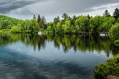 Reflections of green pine trees into a lake under soft greyish c stock photos