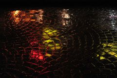 Reflections on Wet Cobblestone Street. Reflections in green and red on wet, rainy street of cobblestone.  Closeup horizontal photo at night Stock Image