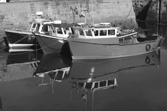 Reflections in the harbour. Reflections of boats tied-up in harbour on calm water Stock Photos