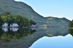 Muckross Lake reflections. Reflections of hills forests and rock formations on calm surface of Muckross Lake in Ireland royalty free stock images