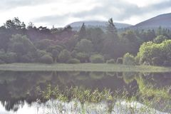 Muckross Lake reflections. Reflections of hills forests and rock formations on calm surface of Muckross Lake in Ireland royalty free stock photography