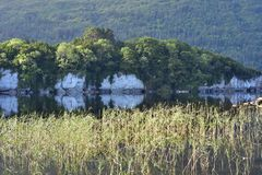 Muckross Lake reflections. Reflections of hills forests and rock formations on calm surface of Muckross Lake in Ireland stock images