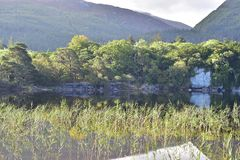 Muckross Lake reflections. Reflections of hills forests and rock formations on calm surface of Muckross Lake in Ireland royalty free stock photos