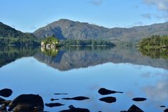 Muckross Lake reflections. Reflections of hills forests and rock formations on calm surface of Muckross Lake in Ireland stock photo