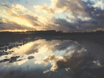 Reflections In A Puddle Of A Beautiful Dramatic Sunset Over A Field Royalty Free Stock Photos